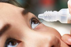 Teen girl drips into the patient eye medication. Stock Image