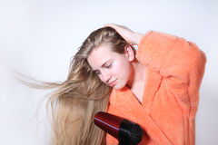 Teen girl drying long wet hair using hairdryer Stock Photo