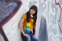 Teen girl with earphones near graffiti wall. Royalty Free Stock Photography