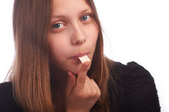 Teen girl eating bubblegum on white background Stock Photos