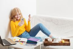 Teen girl eating chocolate and looking at the mobile phone screen. Online education,e-learning stock images