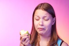 Teen girl eating disgusting apple Stock Photo