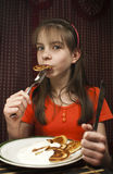 Teen girl eats a pancake. From a dish Stock Photography
