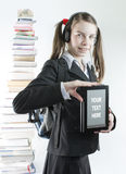 Teen girl with ebook and stack of printed books royalty free stock image