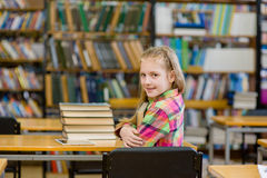 Teen girl embracing book in the library Stock Image