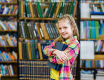 Teen girl embracing book in the library Stock Photo