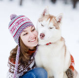 Teen girl embracing cute dog in winter park.  royalty free stock photography