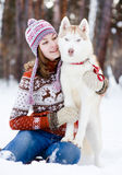 Teen girl embracing cute dog in winter park.  royalty free stock image