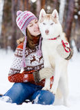 Teen girl embracing cute dog in winter park Royalty Free Stock Photo