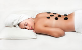 teen girl enjoying a back massage with hot stone in a spa center Stock Photo