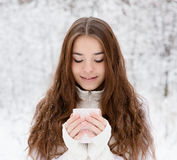 Teen girl enjoying big mug of hot drink during cold day Royalty Free Stock Image
