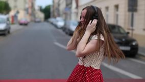 Teen girl enjoying music in headphones, rejoices and dances in the street. stock video footage