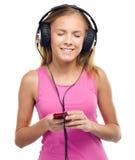 Teen girl enjoying music using headphones. Closeup portrait of lovely teen girl closing her eyes and enjoying music using headphones, isolated over white Stock Photo