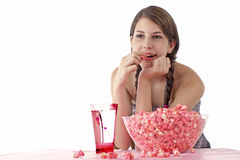 Teen girl enjoys pink popcorn and drink royalty free stock photography