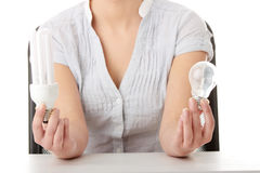 Teen girl environmentalist comparing bulbs Royalty Free Stock Photos