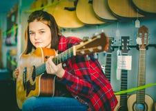 Teen girl examining various acoustic guitars Royalty Free Stock Image