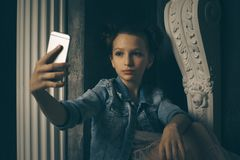 Teen girl excessively sitting at the phone at home. he is a victim of online bullying Stalker social networks. Teen girl excessively sitting at the phone at home Royalty Free Stock Photos