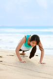 Teen girl exercising on beach near blue ocean waters Royalty Free Stock Image