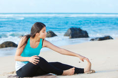 Teen girl exercising on sandy beach of Hawaii near ocean. Beautiful biracial young teen girl sitting on sandy beach in Hawaii with aqua blue ocean water in Royalty Free Stock Image