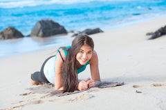 Teen girl exercising on sandy beach of Hawaii near ocean Stock Images