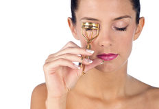 Teen girl with eyelashes curler Royalty Free Stock Image