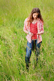Teen Girl in Field Standing Thinking. A pretty somber teenage girl with long brown hair standing in a field of tall grass wearing a red plaid shirt, lost in Stock Photo