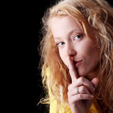 Teen girl with finger on her lips Stock Images