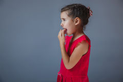 Teen girl fingers in his mouth red dress on a gray Royalty Free Stock Images