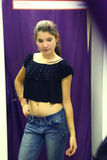 Teen girl in the fitting room fitting new clothes Stock Photography