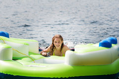 Teen girl floating in a lake. Teenage girl on an inflatable raft in a lake in haliburton ontario canada stock photography