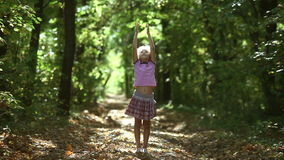 Teen girl  in forest raises his arms to sun. Meditation oneness with nature autumn sunlight  road stock footage