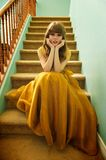 Teen Girl With Formal Prom Gown and Sneakers. Teen girl sits on staircase wearing her formal prom gown and her ratty, old sneakers Royalty Free Stock Photography