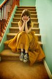 Teen Girl With Formal Prom Gown and Sneakers. Teen girl sits on staircase wearing her formal prom gown and her ratty, old sneakers Royalty Free Stock Image