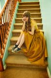 Teen Girl With Formal Prom Gown and Sneakers. Teen girl sits on staircase wearing her formal prom gown and her ratty, old sneakers Stock Photo