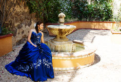 Teen girl in a fountain. Beautiful teen girl with a blue dress siting in a fountain Royalty Free Stock Image