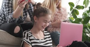 Teen girls browsing their social media content on laptop and mobile phones stock video