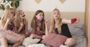 Teen girl friends holding party props and taking selfie at slumber party. Teenage girl friends holding fake party props and taking selfie using mobile phone stock video