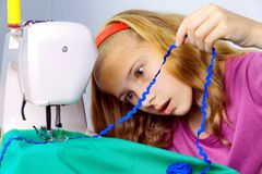 Teen girl frightened by her mistake when sewing Stock Photos