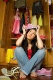 Teen girl in front of open closet. Worried teen girl sitting in front of open closet royalty free stock photos