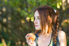 Teen girl in the garden eating Apple royalty free stock photography