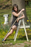 Teen girl with garden tools and ladder Stock Image