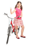 Teen girl giving thumb up and standing by a bike Stock Photos