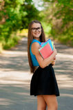 Teen girl with glasses and books in hands Stock Images