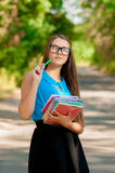 Teen girl with glasses and books in hands Stock Photos