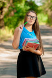Teen girl with glasses and books in hands Stock Image