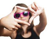 Teen girl with glasses make frame with her fingers Stock Images