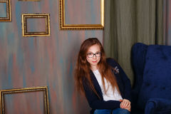Teen girl in glasses sitting in the artist's studio. Royalty Free Stock Photos