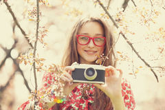 Teen girl in glasses with vintage camera near blossom tree.  Royalty Free Stock Image