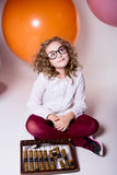Teen girl in glasses with wooden abacus on the background of lar Stock Photos