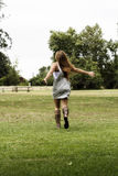 Teen Girl In Gray Dress And Sandals Running On Grass Stock Photos